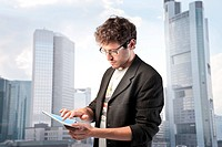 Young businessman using a tablet pc with cityscape in the background