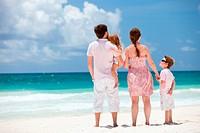 Family of four sitting on Caribbean beach
