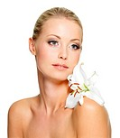 Beauty woman with perfect clean skin and lily flower on shoulder _ isolated