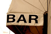 A bar canopy giving shade to outdoor seating