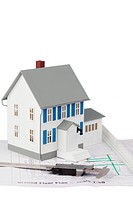 Toy house model and caliper on a ground floor plan against a white background