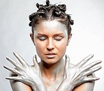 portrait of girl body painted with silver posing on gray