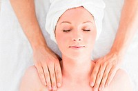 Closeup of a good looking red_haired woman receiving a massage in a spa centre