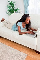 Young woman lying on the sofa using her laptop