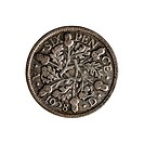 An English sixpence coin dated 1928 on a white background