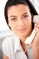 Portrait of smiling attractive woman with landline phone handheld, looking at camera.