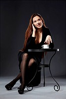 portrait of beautiful girl sitting at the elegant cafe table with a cup of coffee