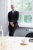 A businessman leaning against a window sill in a conference room