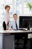 A businesswoman assisting a businessman sitting at a computer