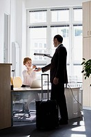 A woman sitting at a desk handing a businessman keys