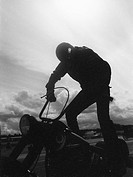 A man standing on a motorcycle (thumbnail)