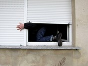 A man climbing through a window