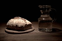 A loaf of bread and a jug of water on a table