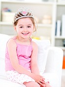 Beutiful pretty little girl with happy smile sitting on the sofa with crown _ indoors