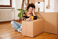 A cheerful woman taking a coffee break while moving house
