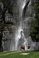 Hikers walking towards a waterfall, Chiavenna, Lombardy, Italy