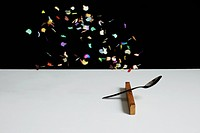 Confetti floating above a spoon leaning on a wooden block