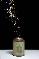 An old_fashioned metal tin and floating confetti