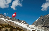 The Swiss flag near the mountain pass Loetschenluecke and the glacier Langgletscher, Loetschental, Valais, Switzerland