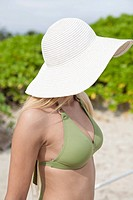 A young woman in a bikini, face obscured by hat