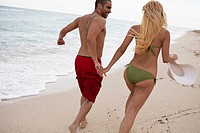 A young couple holding hands and running on the beach