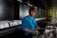 A young man in a record shop, looking at camera (thumbnail)