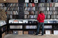Rear view of young man in a record store