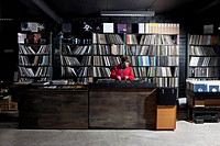 A young man using decks and a sound mixer at a record store