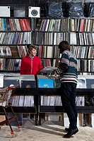 A sales clerk giving a record to a customer in a record store