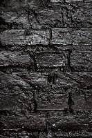 A brick wall painted black, full frame (thumbnail)