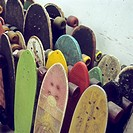 Rows of used skateboards leaning against a wall (thumbnail)