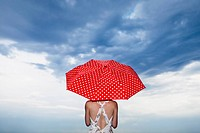 A woman holding a red polka dot umbrella, rear view