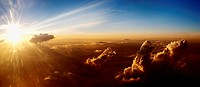 Sun rising on clouds, aerial view