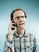 A man using a mobile phone with a confused look on his face (thumbnail)