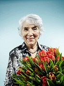 A senior woman receiving a bouquet of tulips