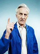 A senior man wearing coveralls and pointing while talking