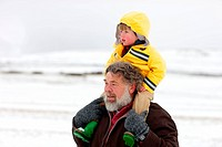 A portrait of a grandfather carrying his grandson on his sholders through the snow, Kamberg, KwaZulu_Natal, South Africa