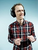 A nerdy guy biting his lip and dancing while listening to headphones