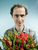 A man holding a bouquet of tulips hopefully