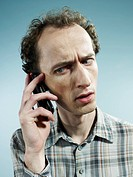 A man using a mobile phone and looking worried