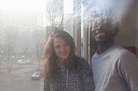 A boyfriend and girlfriend laughing together, viewed through window (thumbnail)