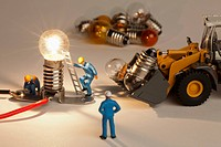 Miniature electrician figurines working on an illuminated light bulb