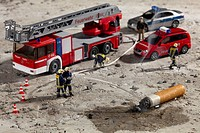 Miniature figurines of firemen using a hose to put out a smoking cigarette butt (thumbnail)