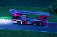 A diorama of a miniature toy fire truck driving on a road at night