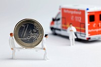 Miniature paramedic figurines carrying a euro coin on a stretcher to a toy ambulance (thumbnail)