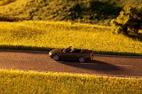A diorama of a miniature man driving a toy convertible sports car on a rural road
