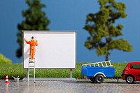 A diorama of a miniature worker billboard posting (thumbnail)