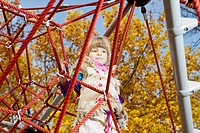 Girl daydreaming on jungle gym