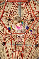 Girl on jungle gym looking up