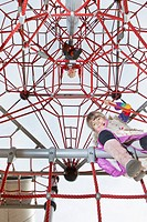 Two kids looking down from jungle gym (thumbnail)